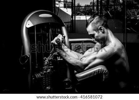 Young muscular man in gym doing exercise. Showing his muscles. - stock photo