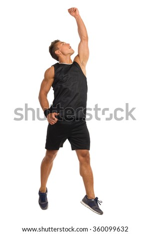 Young muscular man in sport black shirt and shorts posing jumping with arm raised. Front view. Full length studio shot isolated on white. - stock photo