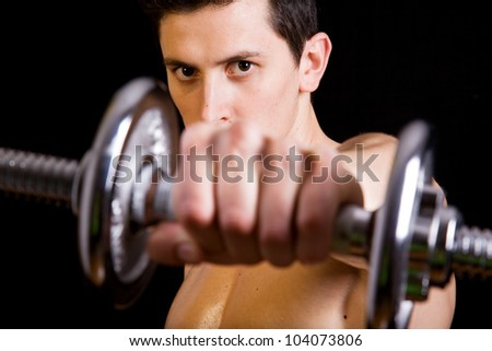 Young muscular man lifting weights on black background - stock photo