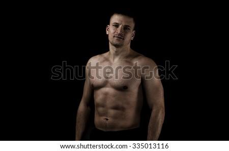 Young muscular man on a black background. Hard light, dark lighting - stock photo