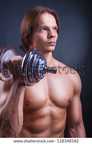 Young muscular man with dumbbell on black background - stock photo