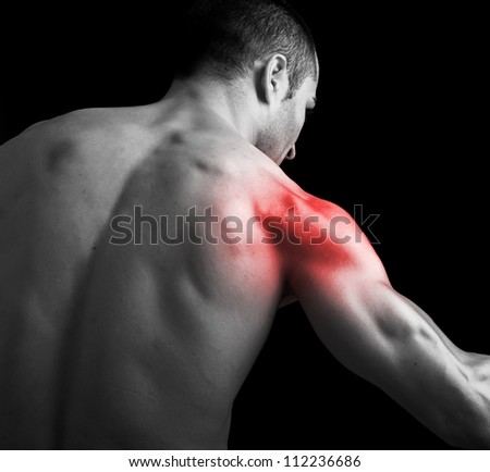 Young muscular man with shoulder pain on black background - stock photo