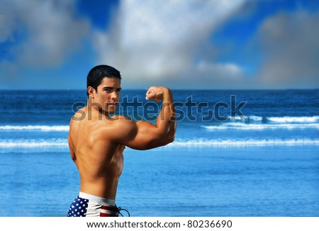 Young muscular sexy male body builder flexing his big bicep on the beach against a bright blue ocean and sky wearing USA flag swim trunks - stock photo