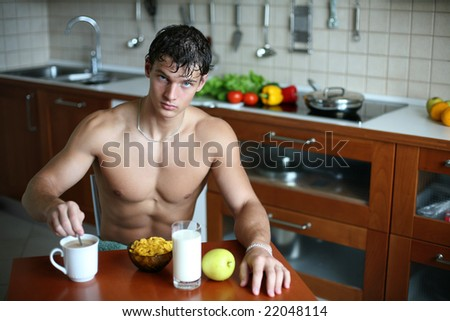 Young muscular sexy man eating his breakfast at the kitchen - stock photo