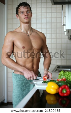 Young muscular sexy man preparing salad at the kitchen - stock photo