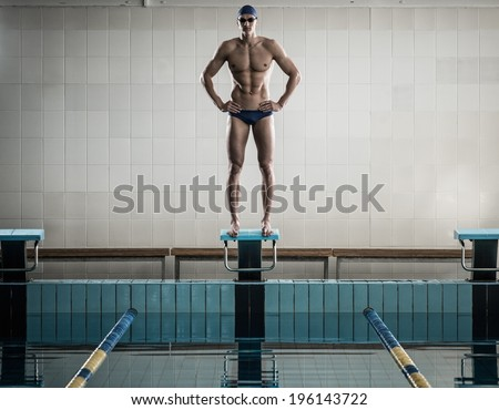 Young muscular swimmer standing on starting block in a swimming pool - stock photo