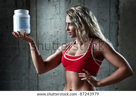 Young muscular woman with sports nutrition.