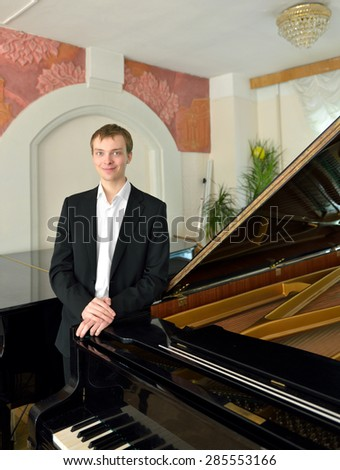 Young musician next to black grand piano - stock photo