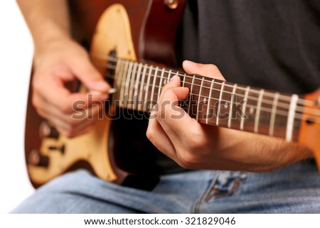 Young musician playing electric guitar close up - stock photo