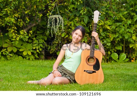 Young musician with a guitar sitting in the park - stock photo