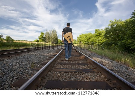 Young musician with guitar on back walking down center of train tracks. - stock photo