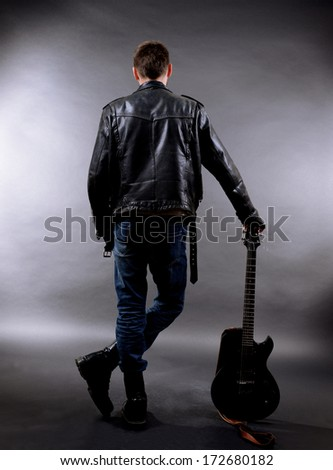 Young musician with guitar on dark color background - stock photo