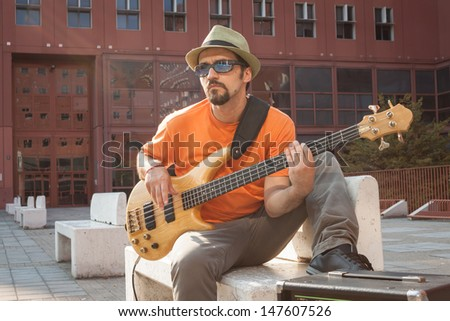 Young musician with hat playing bass guitar on a bench
