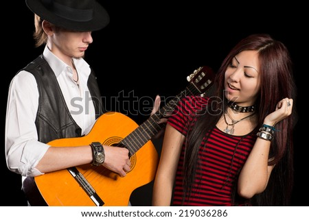 Young musicians perform song. Interracial young couple, Asian woman and Caucasian man.  - stock photo