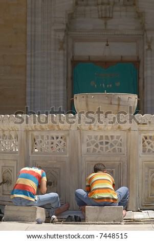 Young muslim boys preparing for the prayer in the courtyard of a mosque