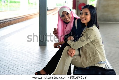 young muslim business woman in head scarf seat together - stock photo