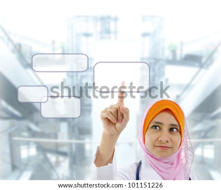Young Muslim female doctor finger pressing on touchscreen monitor button, modern building background - stock photo