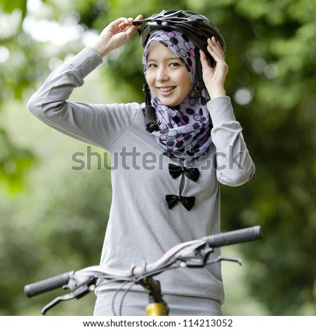 Young Muslim girl on bicycle wearing a helmet - stock photo