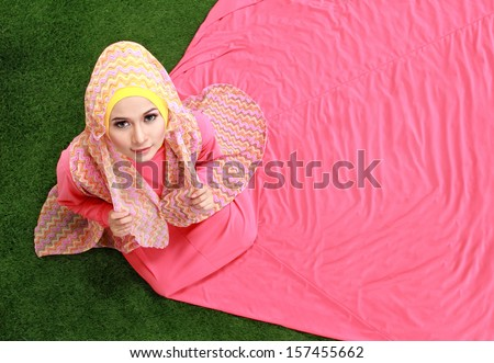Young muslim girl wearing hijab sitting on grass - stock photo
