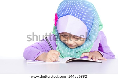 Young muslim girl writing a book on the desk.  Isolated white background - stock photo