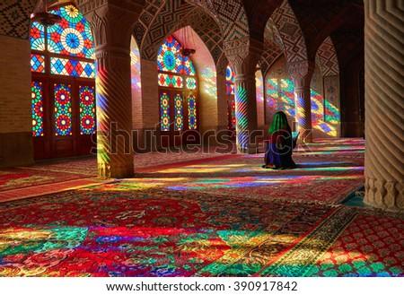 Young Muslim woman praying in Nasir Al-Mulk Mosque (Pink Mosque), Iran, Shiraz - stock photo