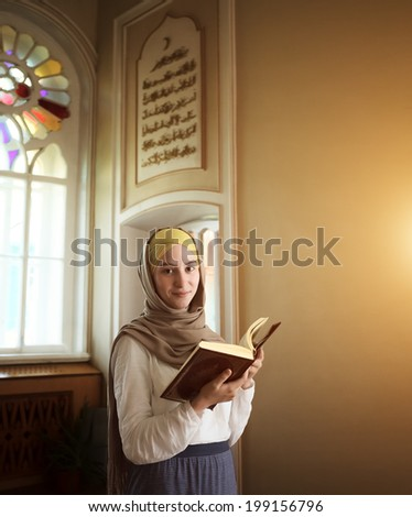 Young muslim woman read Quran in the beautiful mosque at the Ramadan time. - stock photo
