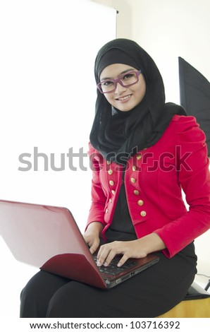 Young Muslim woman sitting with notebook at home. - stock photo