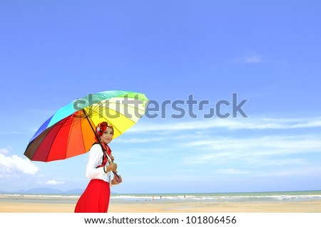 Young Muslim woman with colorful umbrella at beach.