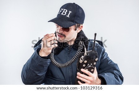 Young mustache FBI agent looking defeated while talking on vintage radio baseball cap - stock photo