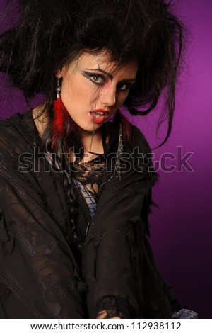 Young mysterious fashion witch against the violet background - stock photo