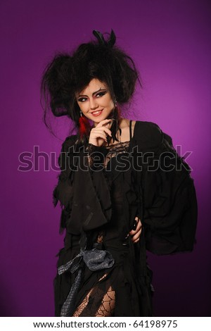 Young mysterious fashion witch isolated on violet background