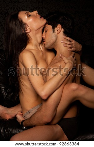 Young naked couple having implied passionate erotic sex, woman in skimpy panties. - stock photo