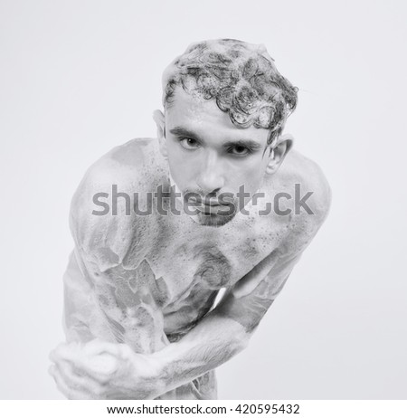 Young naked man taking a shower in the foam with a beautiful body on white background