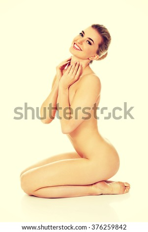 Young naked woman sitting on the floor  - stock photo