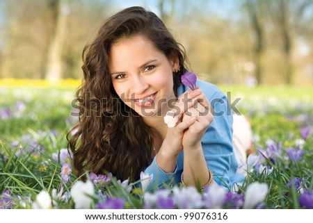 Young natural beauty woman is lying in spring in meadow - stock photo