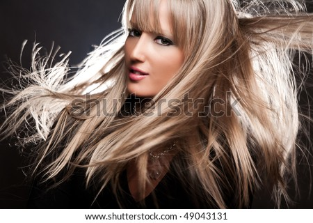 young natural blond woman with hair in motion, studio shot