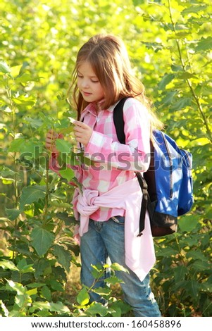 young naturalist studies on the nature of the autumn school lesson in the forest - stock photo