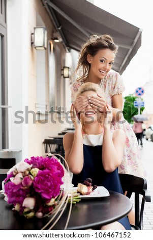 Young naughty girl closes palms of eye of girlfriend and laughs. - stock photo