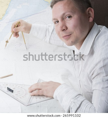young navigator is measuring with divider on navigation map - stock photo