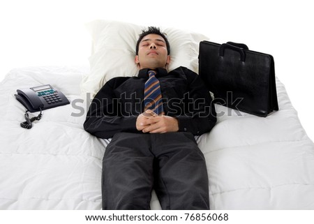Young Nepalese businessman in bed taking a nap between telephone and suitcase. Studio shot. White background. - stock photo
