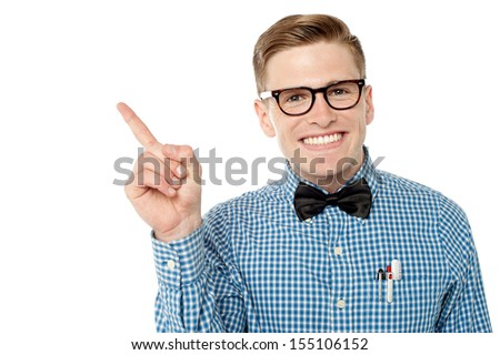 Young nerd pointing towards copy space area - stock photo