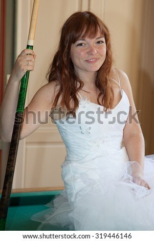 Young newlywed bride playing billiards at her mansion - stock photo