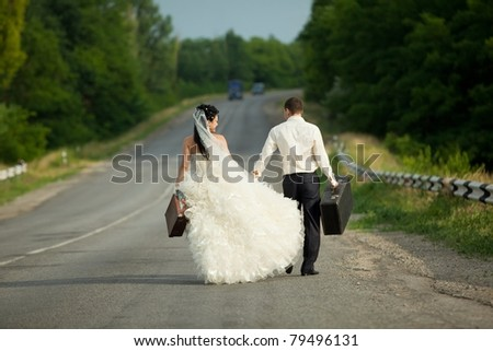 Young newlywed couple holding  suitcases of cash on countryside road - stock photo