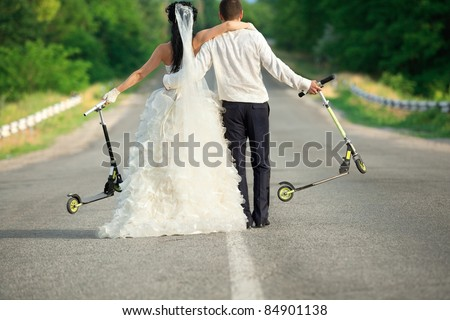 Young newlywed couple with scooter on countryside road - stock photo