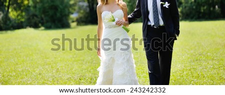 Young newlyweds walking outside.  - stock photo