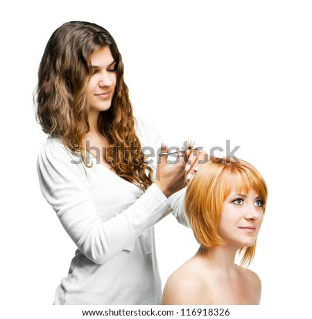 Young nice woman hairdresser makes hairstyle for a girl isolated on white background - stock photo