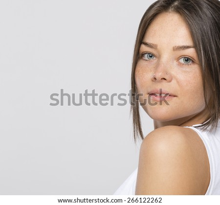 Young, nice woman with freckled skin and piercing in nose - stock photo