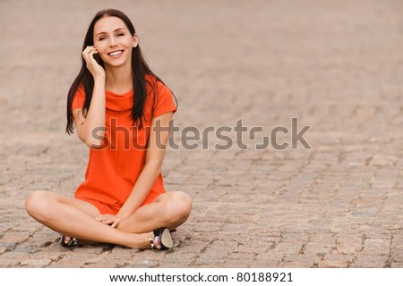 Young nice woman with phone in hands smiles sits in lotus pose on granite roadway. - stock photo