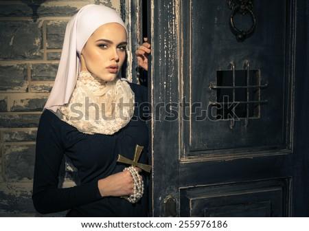 Young nun in the doorway - stock photo