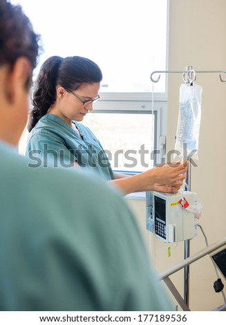 Young nurse adjusting IV bag with coworker in foreground in hospital - stock photo